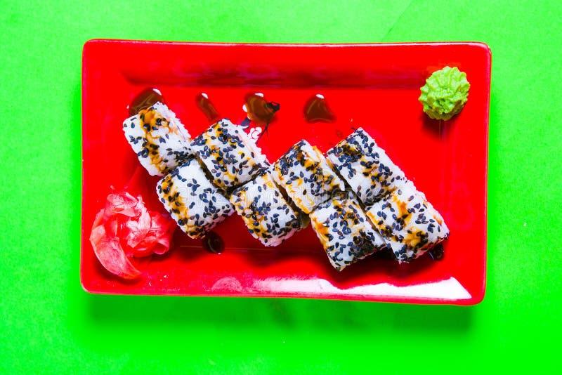 Une partie de sushi d'un plat rouge Fond vert image stock