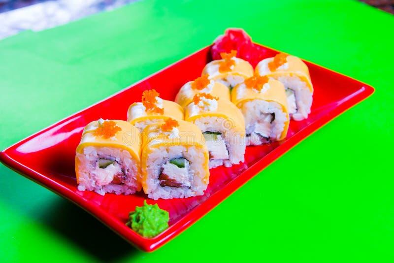 Une partie de sushi d'un plat rouge Fond vert photographie stock