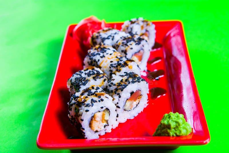 Une partie de sushi d'un plat rouge Fond vert photographie stock libre de droits