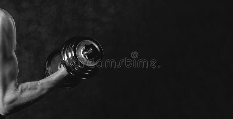 Une partie du corps de l'homme avec l'haltère en métal sur le fond foncé Photographie noire et blanche photos libres de droits