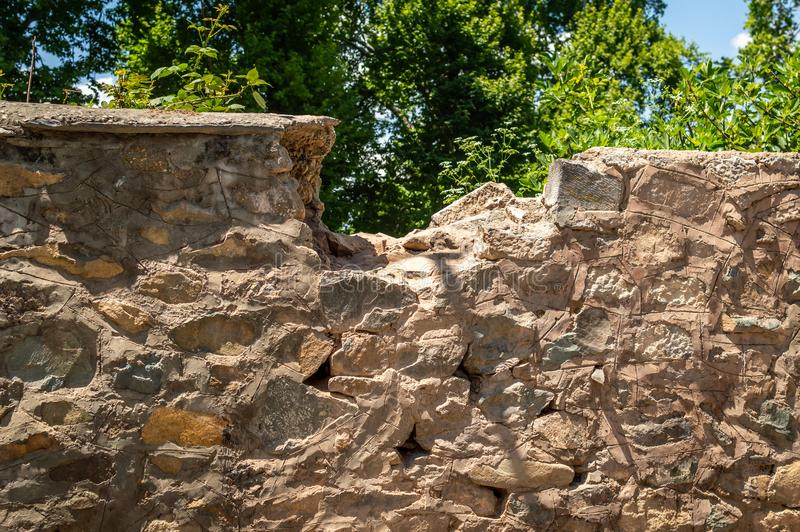 Une partie du dessus d'un mur en pierre est cassée photo stock