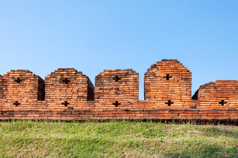 Une partie du mur enrichi antique de ville construit de la brique avec les coupes-circuit et les crenelations croisés d'arc photo stock