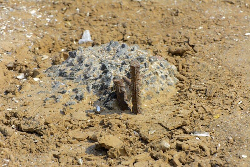 Une partie du pilier concret et un morceau rouillé de bâtons de renfort de fer hors du sable de Yellow Sea image stock