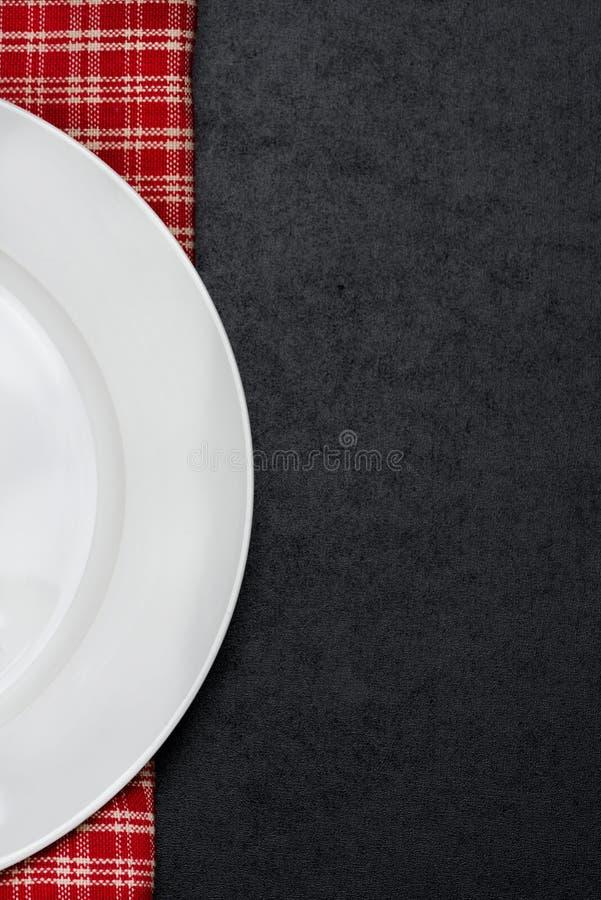 Une partie du plat vide sur une serviette à carreaux, fond noir photos libres de droits