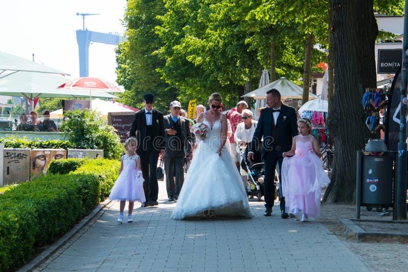 Une partie nuptiale marche le long d'un trottoir de brique après leur cérémonie de mariage photos stock