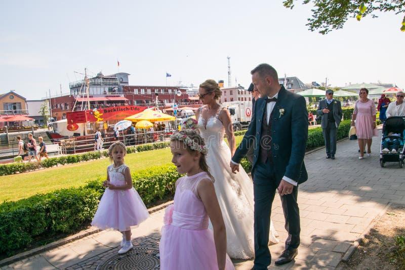 Une partie nuptiale marche le long d'un trottoir de brique après leur cérémonie de mariage photo libre de droits