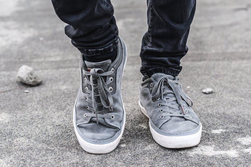 Une partie plus inférieure des jambes masculines dans des espadrilles grises image stock