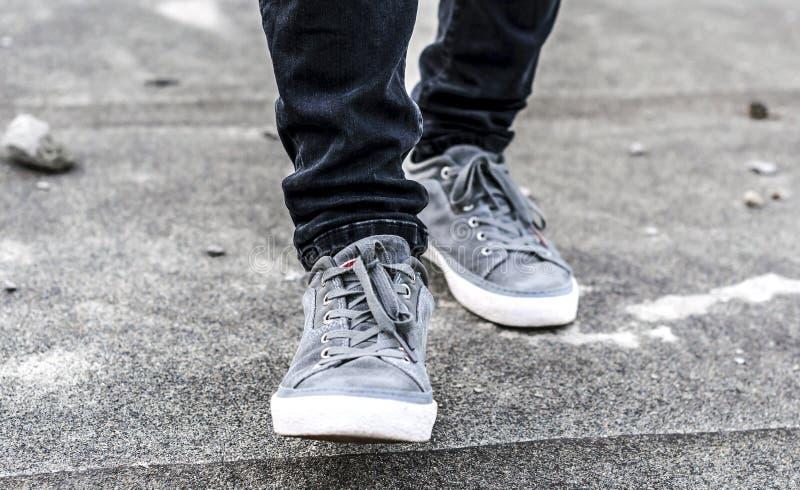 Une partie plus inférieure des jambes masculines dans des espadrilles grises image libre de droits