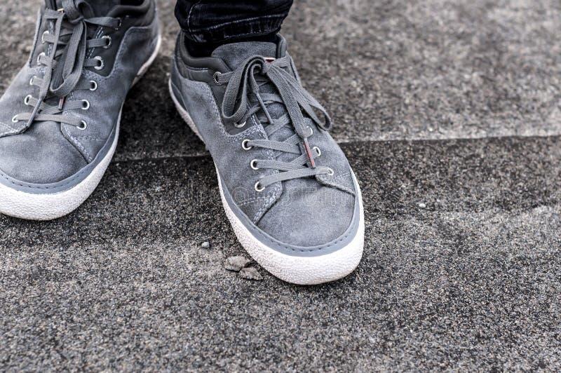 Une partie plus inférieure des jambes masculines dans des espadrilles grises photos libres de droits