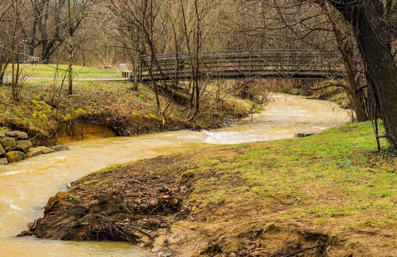 Une passerelle au-dessus de boue lèchent la crique aux hautes eaux photos libres de droits