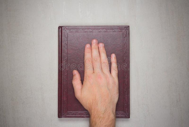 Une paume d'homme sur un livre, un serment sur la bible photographie stock