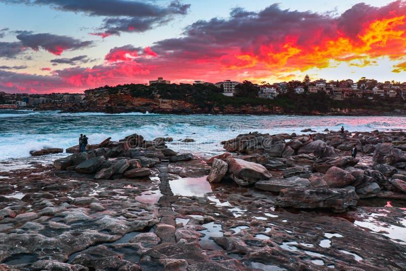 Une peinture des nuages brûlants et la mer et les roches image stock