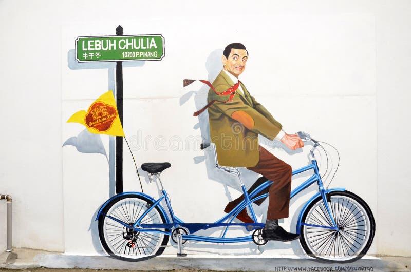 Une peinture murale de M. célèbre Caractère de haricot sur une bicyclette images stock