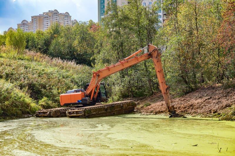 Une pelle flottante nettoie le lit de la rivière photographie stock