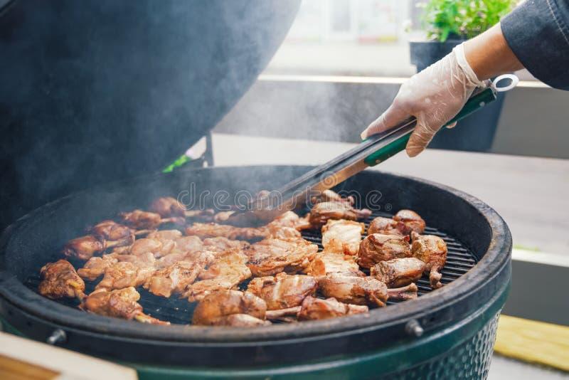 Une personne fait cuire la viande pour le barbecue pour des invités, amis Diner mangeant le concept Buffet de nourriture Diner de image libre de droits