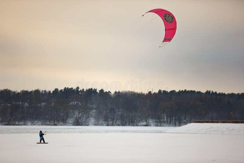 Une personne kiting avec les cerfs-volants colorés en hiver sur la neige image libre de droits