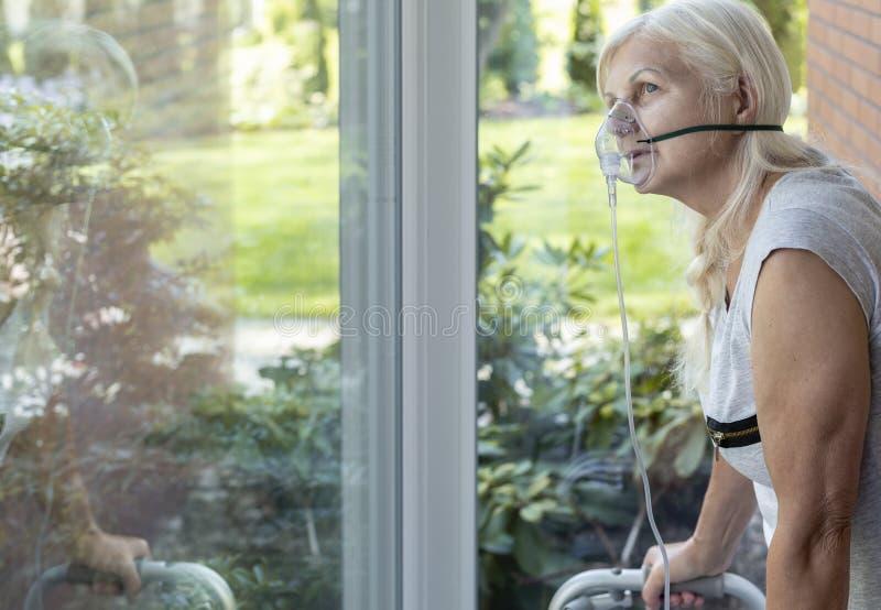 Une personne plus âgée avec un masque respiratoire de l'oxygène regardant une fenêtre image libre de droits