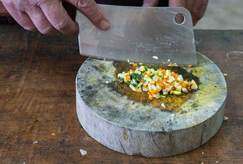 Une personne prépare des légumes sur une planche à découper en bois photos stock
