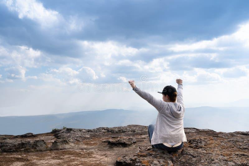 Une personne s'asseyant avec des mains sur la montagne rocheuse photo stock