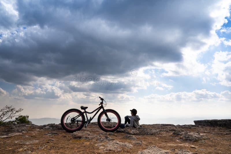 Une personne s'asseyant près d'une bicyclette sur la montagne rocheuse photo stock