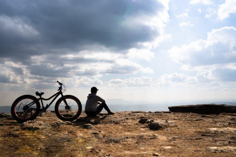 Une personne s'asseyant près d'une bicyclette sur la montagne rocheuse image libre de droits