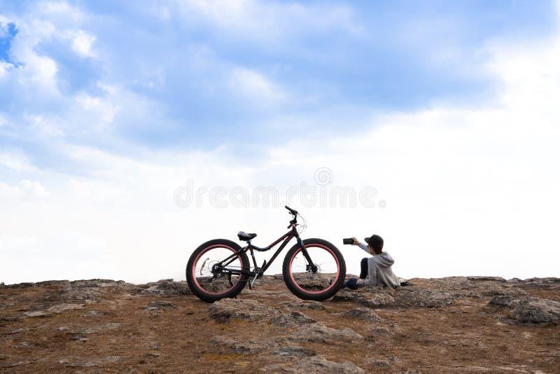 Une personne s'asseyant près d'une bicyclette sur rocheux images libres de droits
