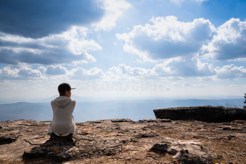 Une personne s'asseyant sur la montagne rocheuse regardant la vue naturelle scénique photo stock