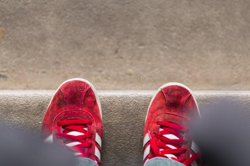 Une personne se tient au bord d'une étape portant les entraîneurs rouges intelligents images stock