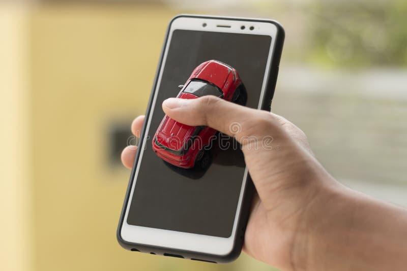 Une personne tient une voiture et un smartphone dans une main Concep images stock