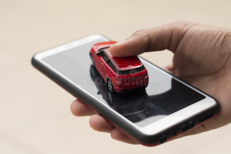 Une personne tient une voiture et un smartphone dans une main Concep photos stock