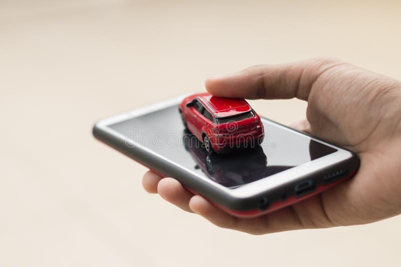 Une personne tient une voiture et un smartphone dans une main Concep photo libre de droits
