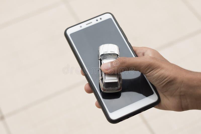 Une personne tient une voiture et un smartphone dans une main Concep image libre de droits