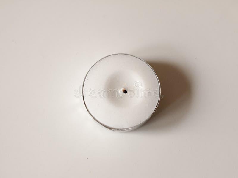 Une petite bougie blanche de cire en cercle à base métallique avec la mèche noire photos libres de droits