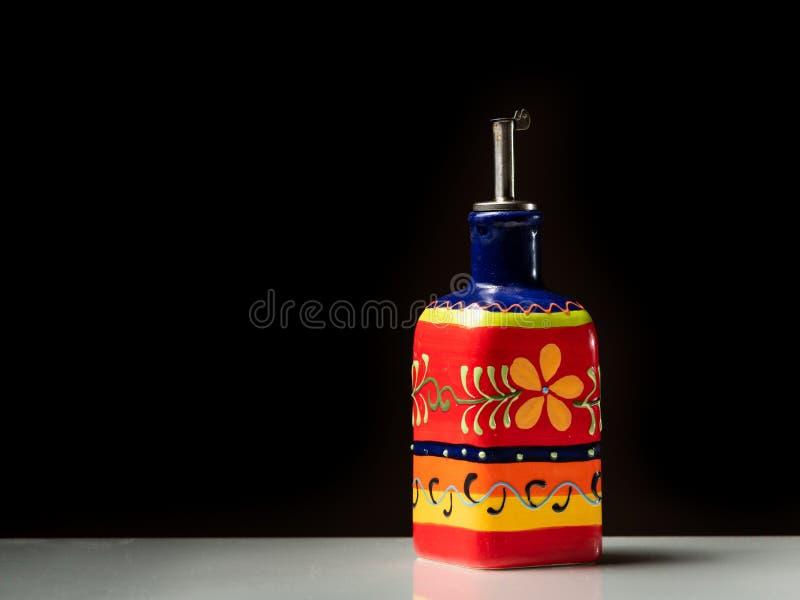 Une petite bouteille peinte rouge pour servir l'huile d'olive photographie stock
