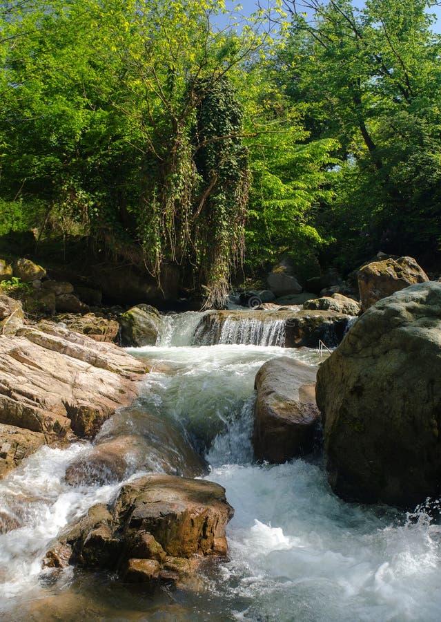 Une petite cascade parmi les roches sur la rivière de montagne images libres de droits