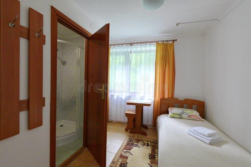 Une petite chambre d'hôtel avec une salle de bains combinée Et un lit photo stock