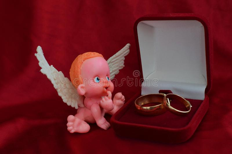 Une petite figure d'un ange se reposant près d'une fin de boîte à bijoux sur le fond rouge photographie stock