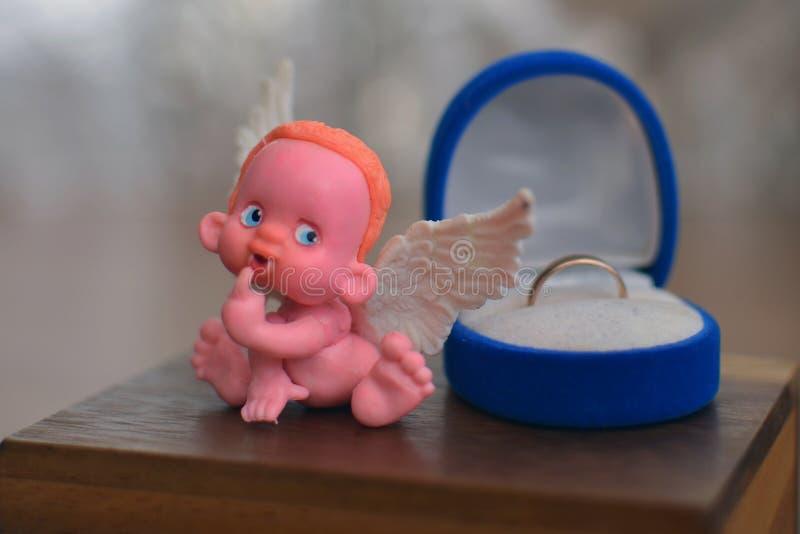 Une petite figure d'un ange se reposant sur ou près d'une fin de boîte à bijoux  image libre de droits
