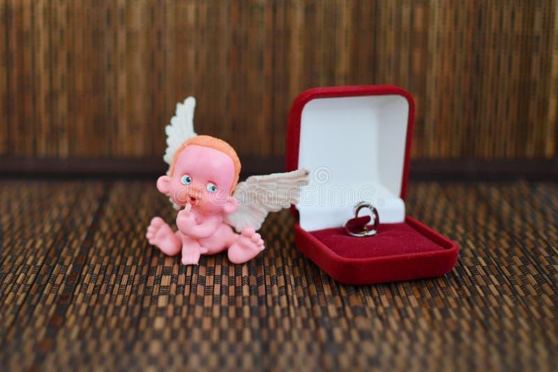 Une petite figure d'un ange se reposant sur ou près d'une fin de boîte à bijoux  photos stock