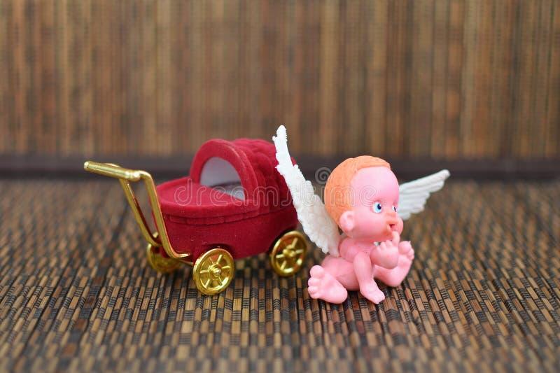 Une petite figure d'un ange se reposant sur ou près d'une fin de poussette de boîte à bijoux  photos stock