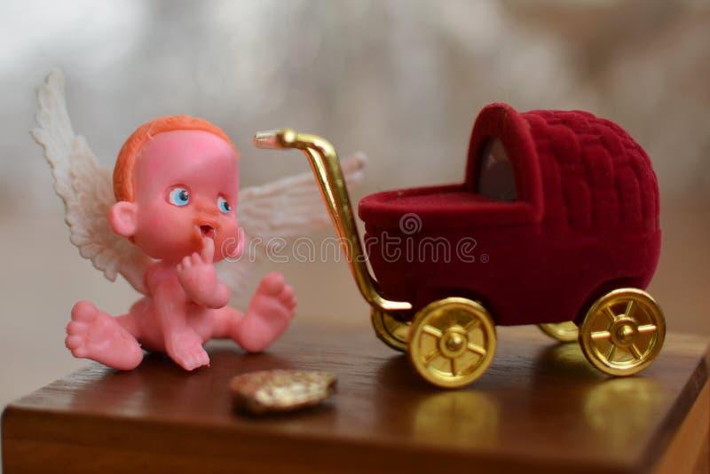 Une petite figure d'un ange se reposant sur ou près d'une fin de poussette de boîte à bijoux  images stock
