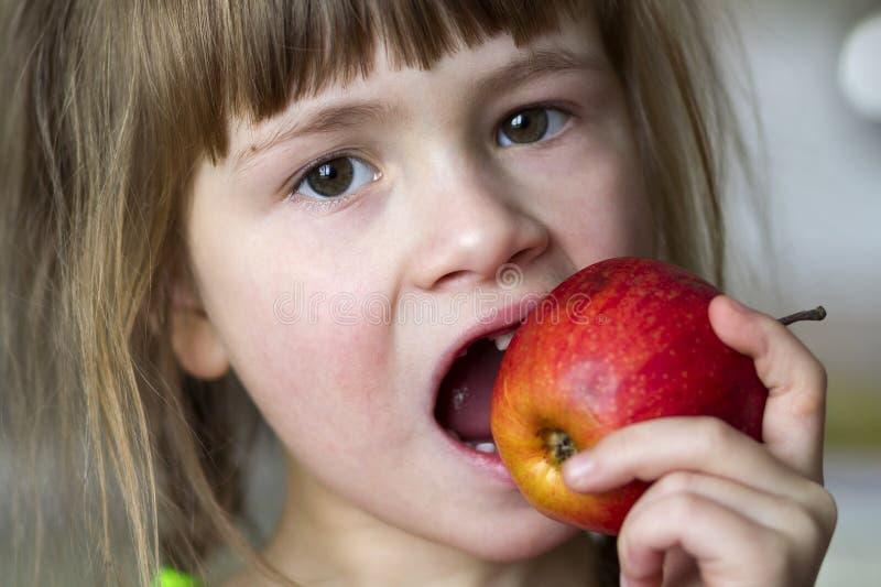 Une petite fille édentée bouclée mignonne sourit et tient une pomme rouge photographie stock libre de droits