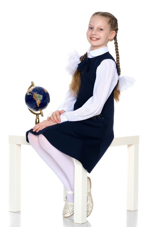 Une petite fille étudie le globe photos stock
