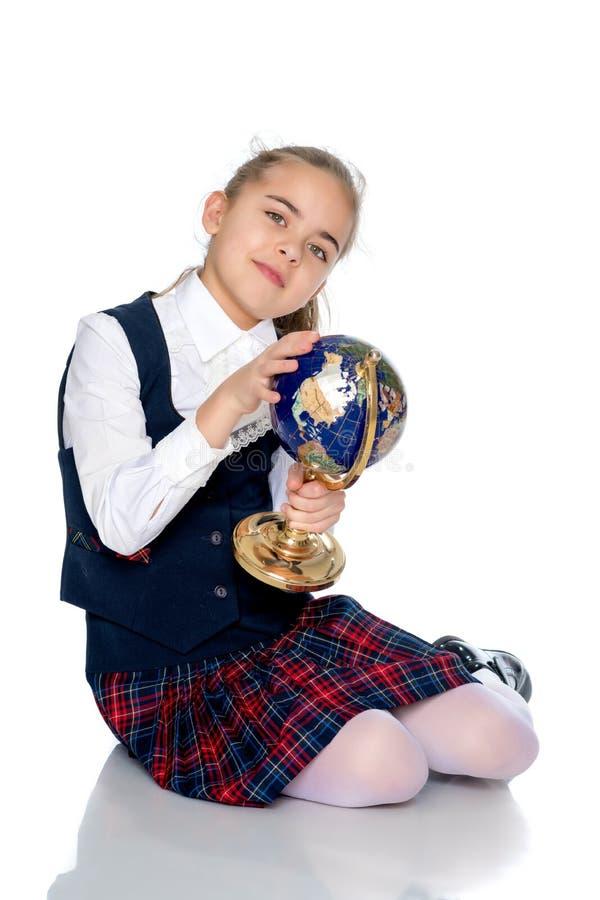 Une petite fille étudie le globe image stock