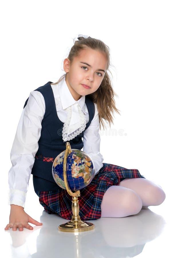 Une petite fille étudie le globe photo stock