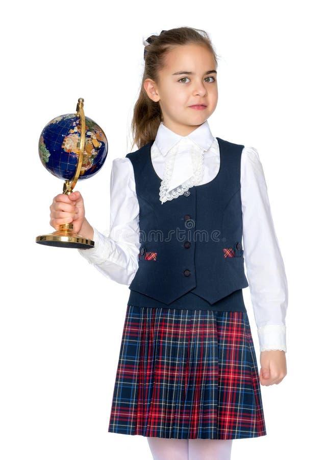 Une petite fille étudie le globe photographie stock