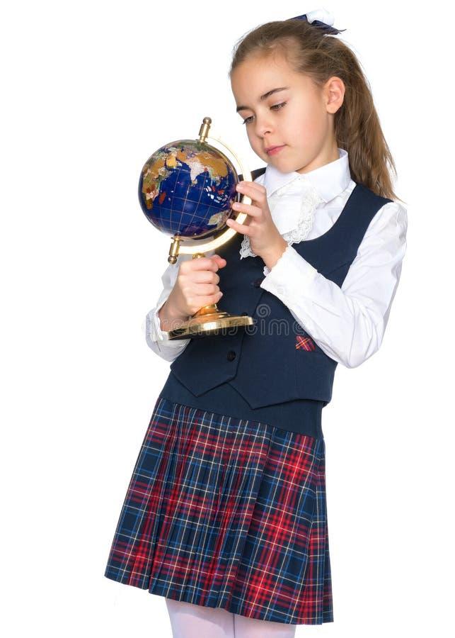 Une petite fille étudie le globe images libres de droits