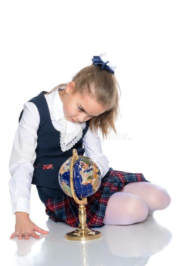 Une petite fille étudie le globe photographie stock libre de droits