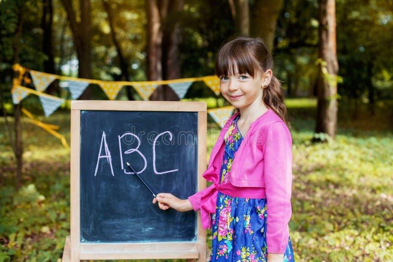 Une petite fille étudie près du tableau noir De nouveau ? l'?cole Le concept de l'éducation, école, enfance images stock