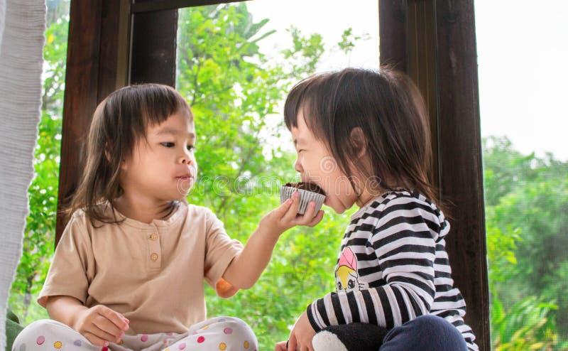 Une petite fille asiatique et sa soeur mangent du cupcake à la banane dans la pièce avec délice image stock